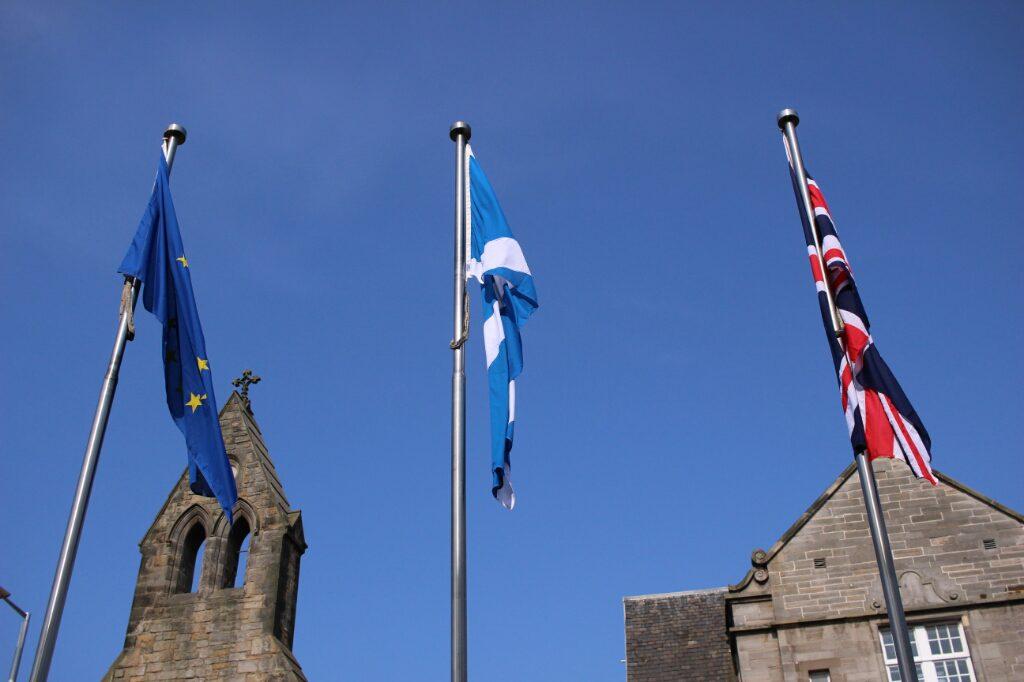 Noch hängen sie einträchtig nebeneinander: Die Flagge der Europäischen Union neben der britischen. Dazwischen die schottische, denn das Bild wurde vor dem schottischen Parlament in Edinburgh aufgenommen.